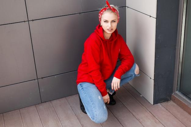 Jeune femme élégante moderne en bottes noires dans un sweat-shirt rouge en jeans déchirés avec un bandana à la mode assis à l'extérieur près d'un mur gris