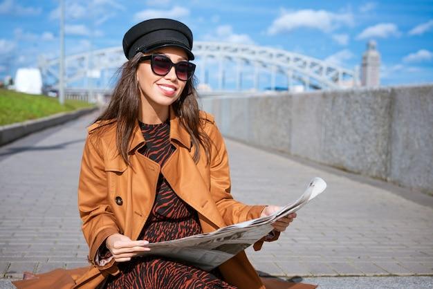 Une jeune femme élégante d'origine caucasienne lit un journal frais dans des lunettes de soleil et une belle casquette noire...