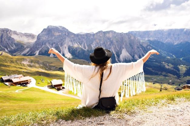 Jeune femme élégante posant dans les montagnes des alpes en tenue de mode boho