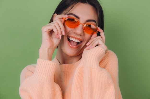 Jeune femme élégante en pull pêche occasionnel et lunettes orange isolé sur mur d'olive verte heureux rire souriant positif autour de l'espace de copie