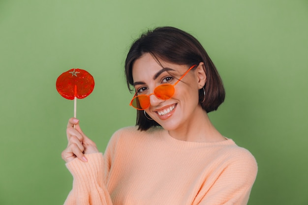 Jeune femme élégante en pull pêche occasionnel et lunettes orange isolé sur mur d'olive verte avec sucette orange sourire positif copie espace
