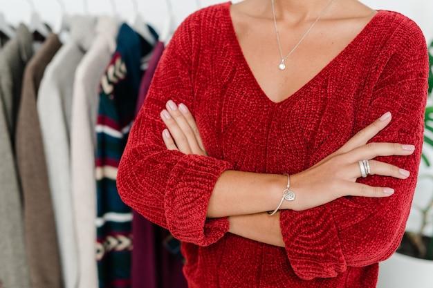 Jeune femme élégante en pull tricoté rouge traversant les bras par la poitrine