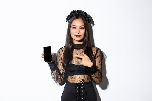 Jeune femme élégante en robe gothique et couronne noire pointng doigt sur l'écran du smartphone avec un sourire heureux sur son visage, debout sur fond blanc.