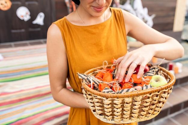 Jeune femme élégante en robe jaune tenant le panier avec des friandises d'halloween enveloppées dans des emballages rayés et orange préparés pour les enfants