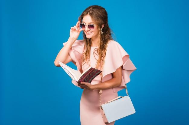 Jeune femme élégante en robe de luxe rose lisant un livre