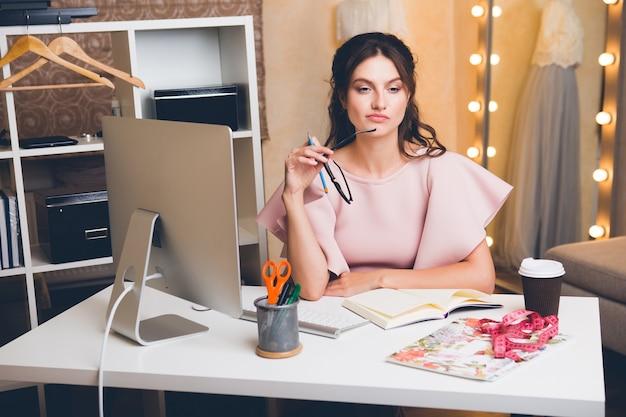 Jeune femme élégante en robe de luxe rose travaillant au bureau sur ordinateur