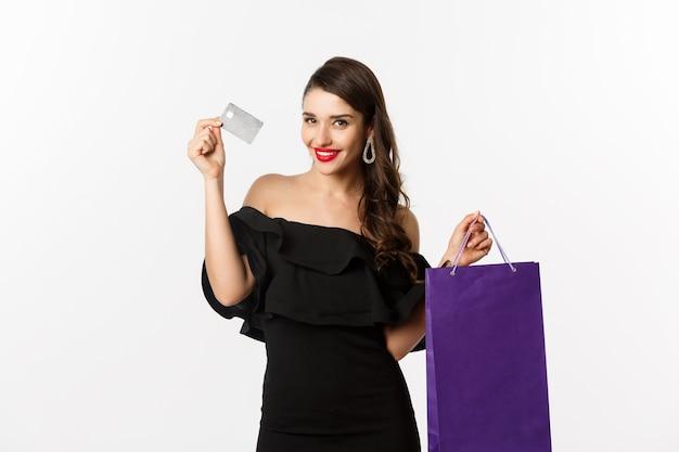 Jeune femme élégante en robe noire faisant du shopping, tenant un sac et une carte de crédit, souriante heureuse, debout sur fond blanc