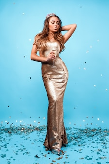 Jeune femme élégante en robe à paillettes dorées, maquillage de soirée, tenant une coupe de champagne et célébrant...