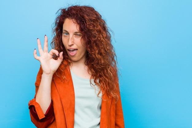 Jeune femme élégante rousse cligne de l'œil et tient un geste correct avec la main