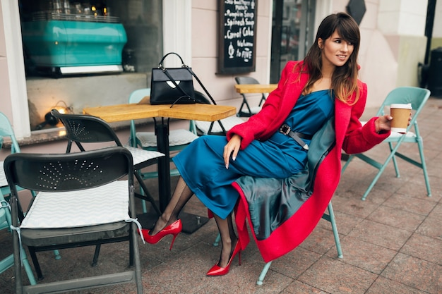 Jeune femme élégante et séduisante assise dans le café de la rue de la ville en manteau rouge, boire du café portant une robe bleue