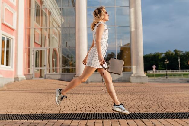 Jeune femme élégante et séduisante en cours d'exécution sautant drôle dans des baskets dans la rue de la ville en robe blanche de style de mode d'été portant des lunettes de soleil et un sac à main