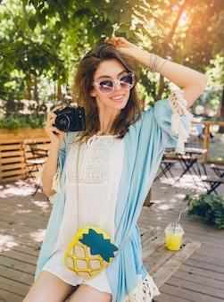 Jeune femme élégante et séduisante dans le parc, style de rue, tendance de la mode estivale, cape bleue, robe boho blanche, accessoires, tenant un appareil photo vintage, souriant, émotion heureuse, profitant d'une chaude journée ensoleillée