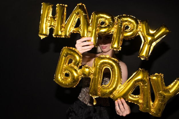 Jeune femme élégante tenant des ballons en forme de lettre de couleur dorée tout en vous félicitant pour votre anniversaire sur fond noir