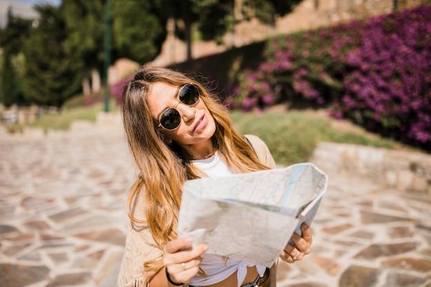 Jeune femme élégante tenant la carte debout dans le parc