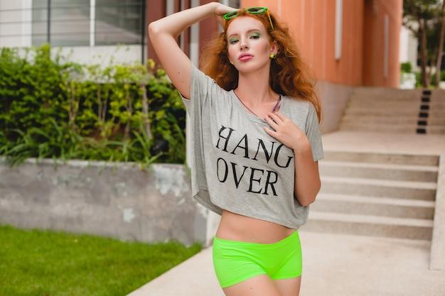 Jeune femme élégante en vêtements de fitness, cheveux roux, shorts verts, lunettes de soleil, t-shirt surdimensionné, pendre, ambiance de fête. s'amuser, sexy, chaud, coquin, corps mince, athlétique,