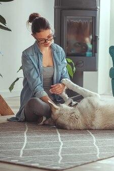 Jeune Femme élevant Et Jouant Avec Son Chien Domestique Husky Sibérien à La Maison Photo Premium