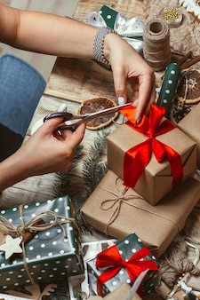 Jeune femme d'emballage et décore beaucoup de pile de cadeaux