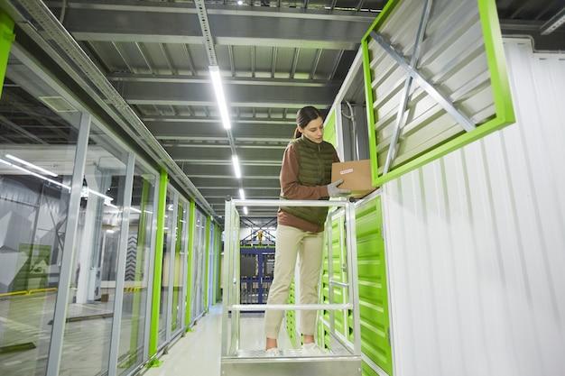 Jeune femme emballant des boîtes dans une boîte de rangement tout en travaillant dans un entrepôt