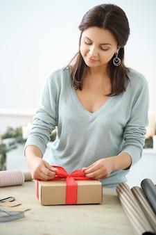 Jeune femme emballant des cadeaux de noël