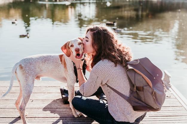 Jeune femme embrassant son chien à l'extérieur dans un parc avec un lac. journée ensoleillée, saison d'automne