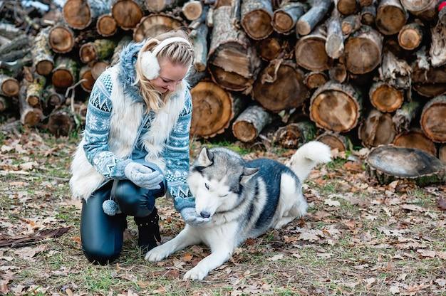 Jeune femme embrassant son chien husky