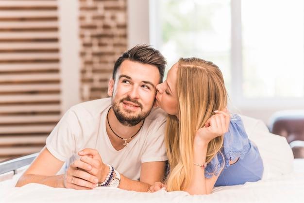 Jeune femme embrassant son petit ami allongé sur le lit dans la chambre