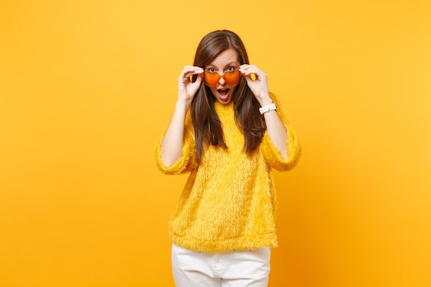 Jeune femme émerveillée et excitée en pull de fourrure, pantalon blanc tenant et enlevant des lunettes orange coeur isolées sur fond jaune vif. les gens émotions sincères, concept de style de vie. espace publicitaire.