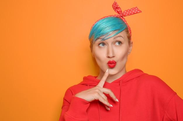 Jeune femme émotionnelle avec des cheveux inhabituels sur la couleur