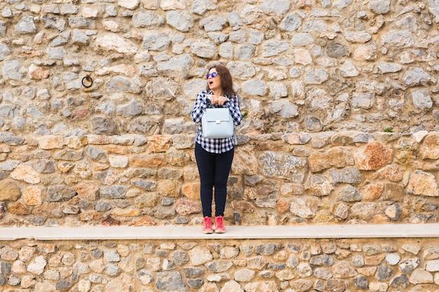 Jeune femme émotionnelle drôle avec sac à main posant sur fond urbain en pierre