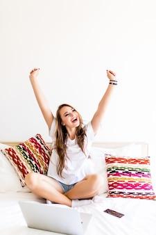 Jeune femme avec des émotions de victoire avec ordinateur portable au lit à la maison