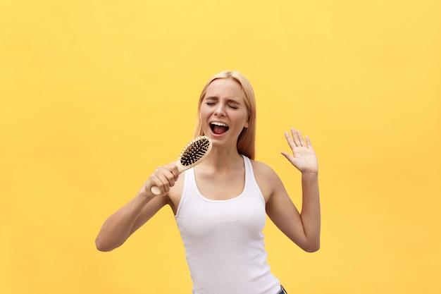 Jeune femme émotive chantant avec un peigne en s'habillant. isolé sur fond jaune.