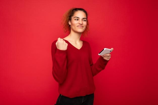 Jeune femme émotive portant un pull rouge foncé isolé sur fond rouge tenant un smartphone s'amusant et montrant un geste oui regardant sur le côté.