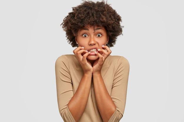 Jeune femme émotive stressante garde les mains près de la bouche