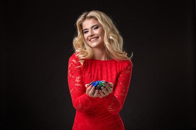 Jeune femme émotive tenant un tas de jetons dans ses mains poker