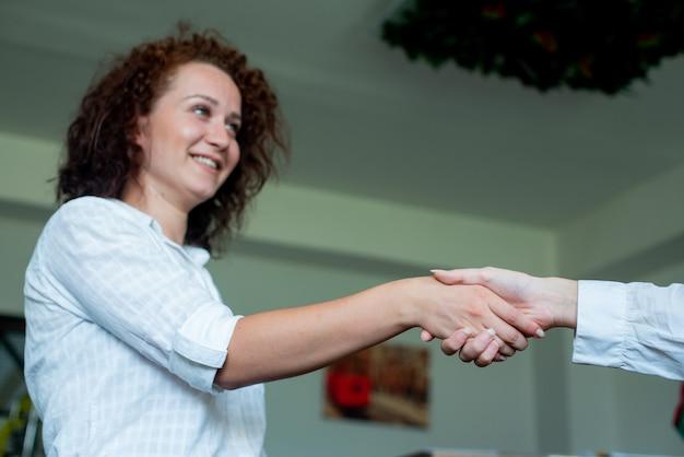 Jeune femme employé de bureau souriant sympathique serrant la main avec un collègue debout sur le bureau