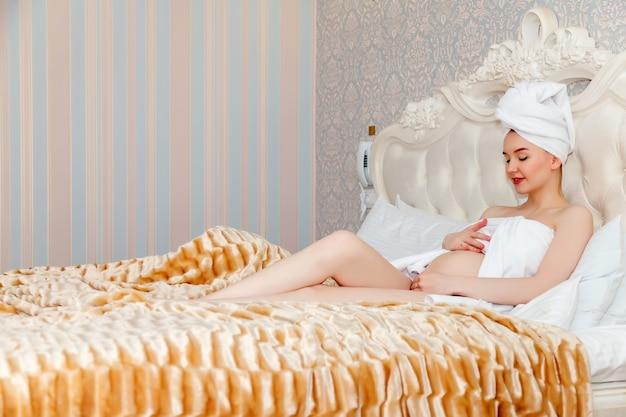 Jeune femme enceinte apparence slave après la douche, allongée sur le lit serrant votre ventre arrondi dans la chambre d'hôtel. lait de grossesse