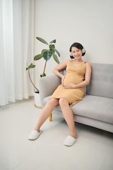 Jeune femme enceinte appréciant la chanson préférée à la maison