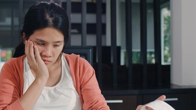 Jeune femme enceinte asiatique répertorie les revenus et les dépenses à la maison. maman inquiète, sérieuse, stressée tout en enregistrant un budget, une taxe, un document financier dans le salon à la maison.
