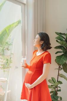 Jeune femme enceinte asiatique tenant un verre de lait en se tenant debout derrière la fenêtre.