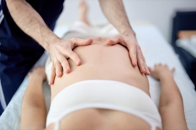 Jeune femme enceinte avec une belle peau allongée sur le lit ayant un massage prénatal relaxant, physiothérapeute faisant diverses techniques pour un meilleur massage, photo en gros plan des mains sur le ventre