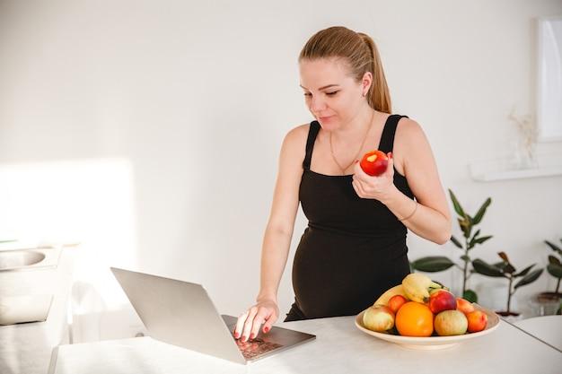 Jeune femme enceinte blonde en robe noire dans une cuisine blanche, manger des fruits et regarder un ordinateur portable