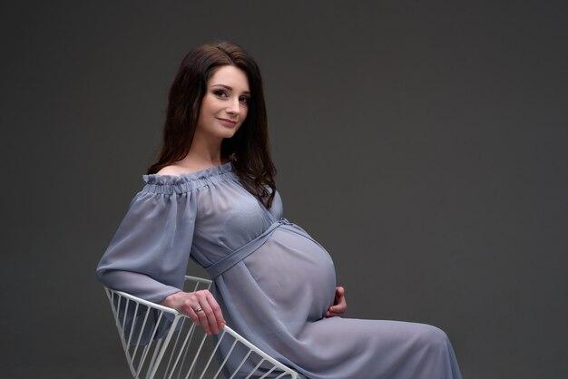 Jeune femme enceinte dans une robe est assise sur une chaise
