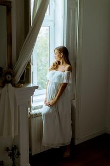 Jeune femme enceinte debout près de la fenêtre