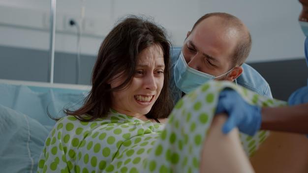 Jeune femme enceinte donnant naissance à un enfant fatigué