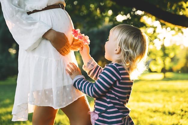 Jeune femme enceinte avec enfant à l'extérieur dans le pré mère et fille sur la nature