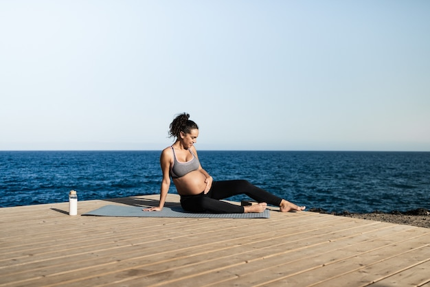 Jeune femme enceinte faisant du yoga en plein air