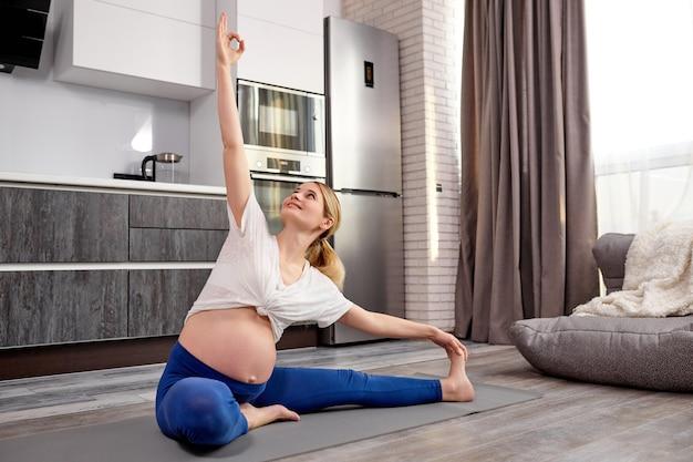 Jeune femme enceinte faisant des exercices de fitness et de yoga sur un tapis gris à la maison