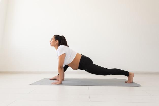 Jeune femme enceinte flexible faisant de la gymnastique sur un tapis sur le sol sur fond blanc le concept