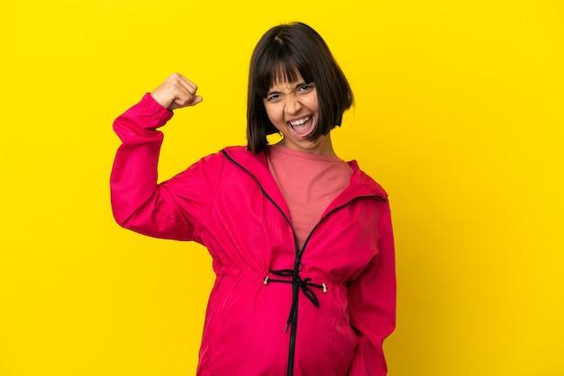 Jeune femme enceinte sur fond jaune isolé célébrant une victoire