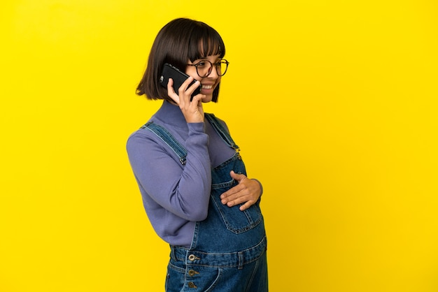 Jeune femme enceinte sur fond jaune isolé en gardant une conversation avec le téléphone mobile